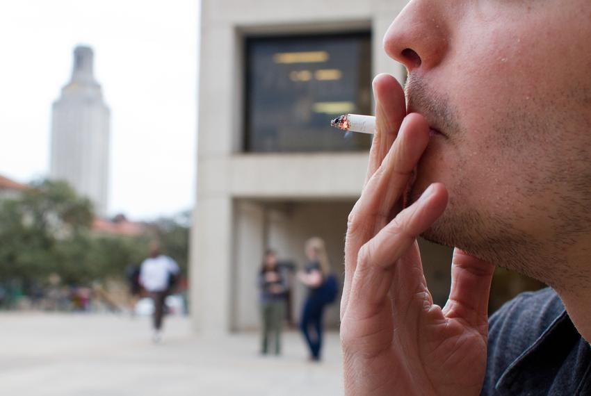 A student  smokes a cigarette on the College of Communication plaza.