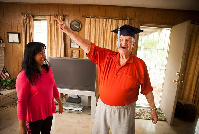 Robert Titus tries on his graduation cap with the help of his wife, Jennifer, in his Houston home on Nov. 26, 2012. Titus ...