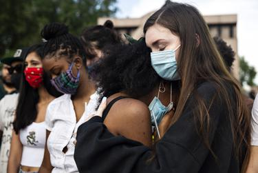 Taylor Putnam comforts her friend Veronica Holmes at a vigil honoring those whose lives were lost to police shootings at Freedman's Memorial Cemetery on May 31.