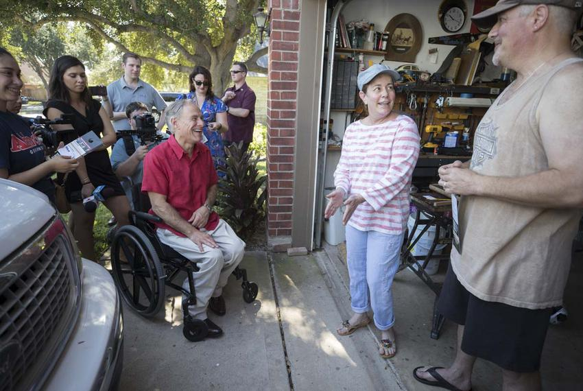 Texas Gov. Greg Abbott greets Wendy Randall and husband Martin during a block walk the day after his re-election announcemen…