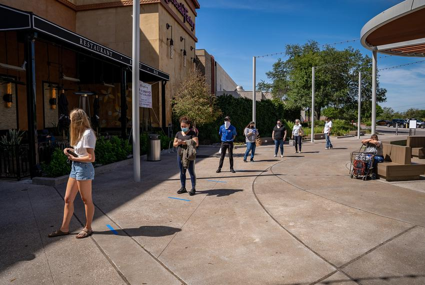 Customers practice social distancing as they wait for the Barton Creek Square Mall in Austin to open on May 1, 2020.