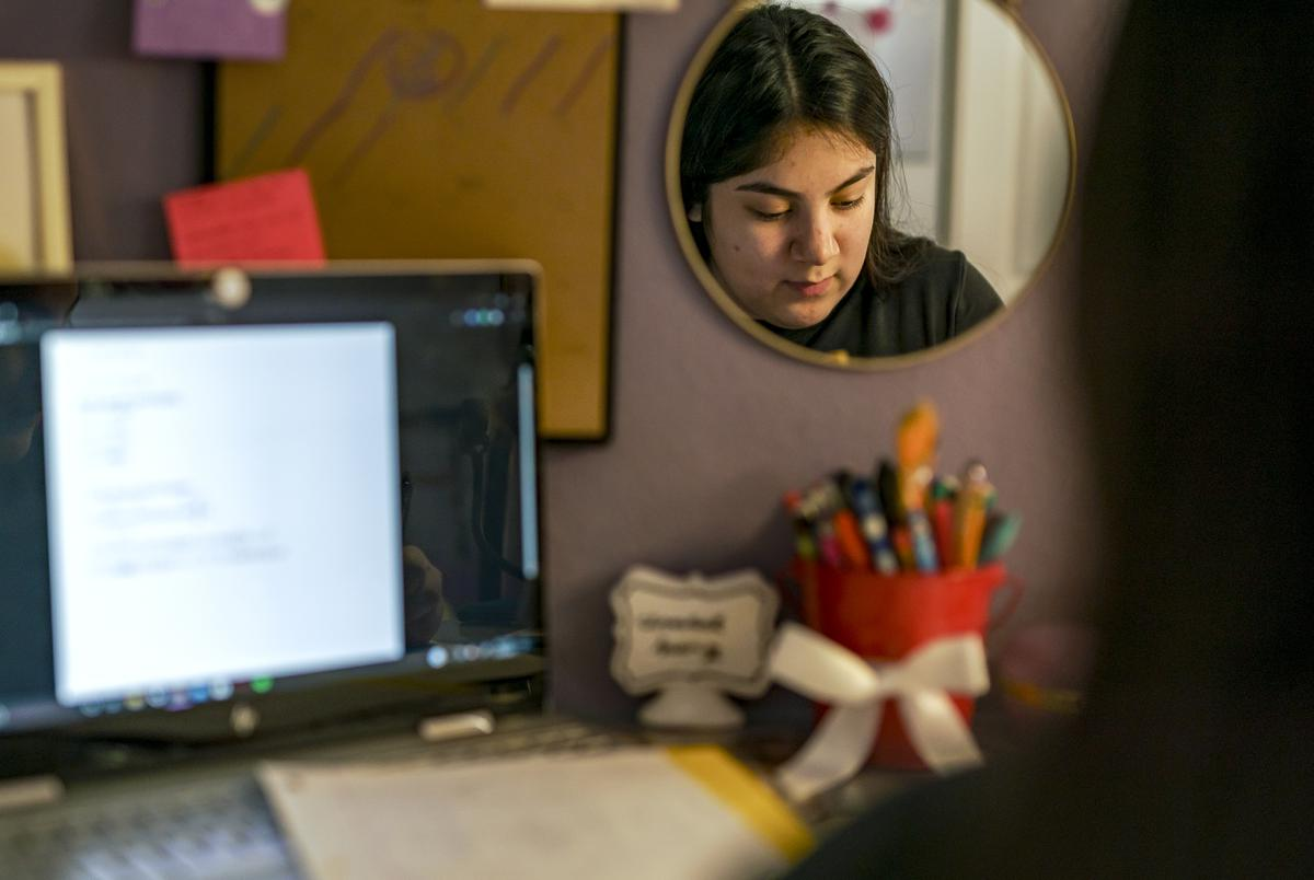 Before the start of the school day, Isabel Suarez works on homework from her home in Pflugerville. Dec. 9, 2020.