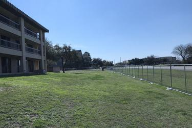 A temporary fence erected around the quarantined hotel on Lackland Air Force Base.