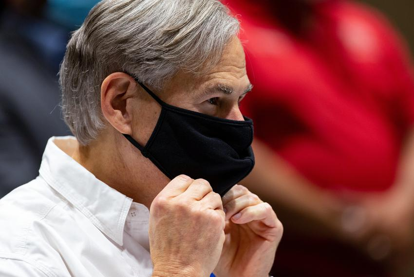 Gov. Greg Abbott puts on his mask during his press conference after talking to local and county officials about the damage d…