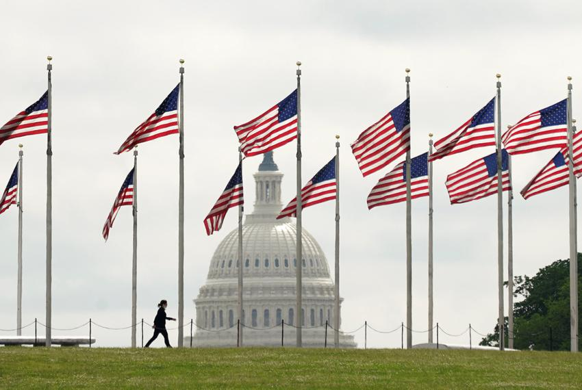 The U.S. Capitol looms in the background as a woman walks among flags at the Washington Monument in Washington D.C. on May 2…