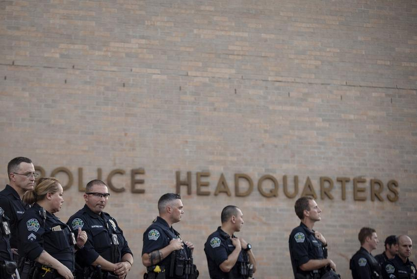 Austin police officers stand guard outside of their headquarters during a protest over the death of George Floyd. Floyd died…