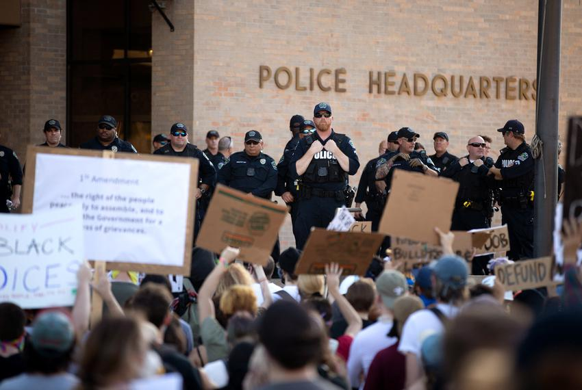 Police look on demonstrators gathered outside Austin Police headquarters for another night of protest against police violenc…