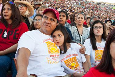 Adrian Jimenez embraces his daughter, Katrina Jimenez as they watch Pope Francis give Mass on TV during the Two Nations One Faith event held at Sun Bowl Stadium on Wednesday, February 17, 2016 in El Paso. Parishioners packed the stadium to watch the live broadcast of Pope Francis' Mass being held in El Paso's neighboring city of Ciudad Juarez.