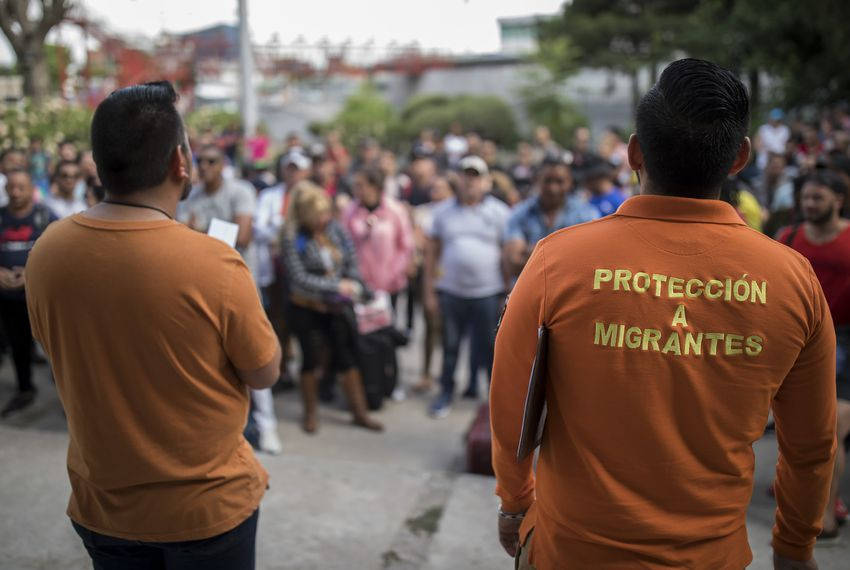 Workers from the Centro de Atención Integral a Migrantes (CAIM) call out numbers from the asylum waiting list outside the center in Ciudad Juárez on May 13, 2019.