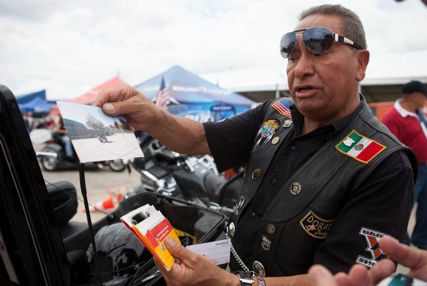 Jorge Rojas Lopez of the Dorados De Villa motorcycle club displays photographs of his fellow riders at the Republic of Texas…