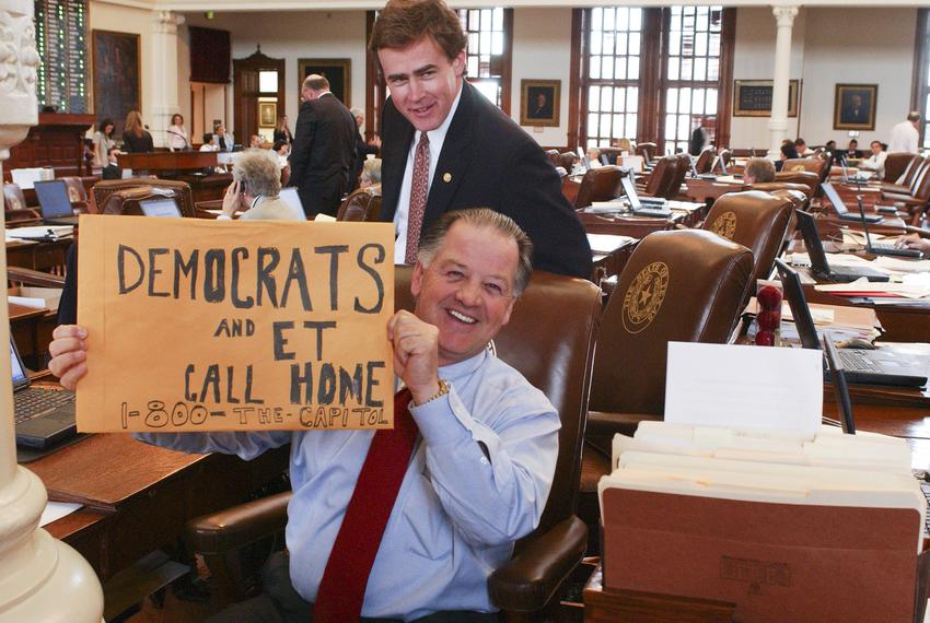 State Rep. Tommy Merritt, R-Longview holds a sign while Rep. Dan Branch, R-Dallas watches during the Texas House Democratic …