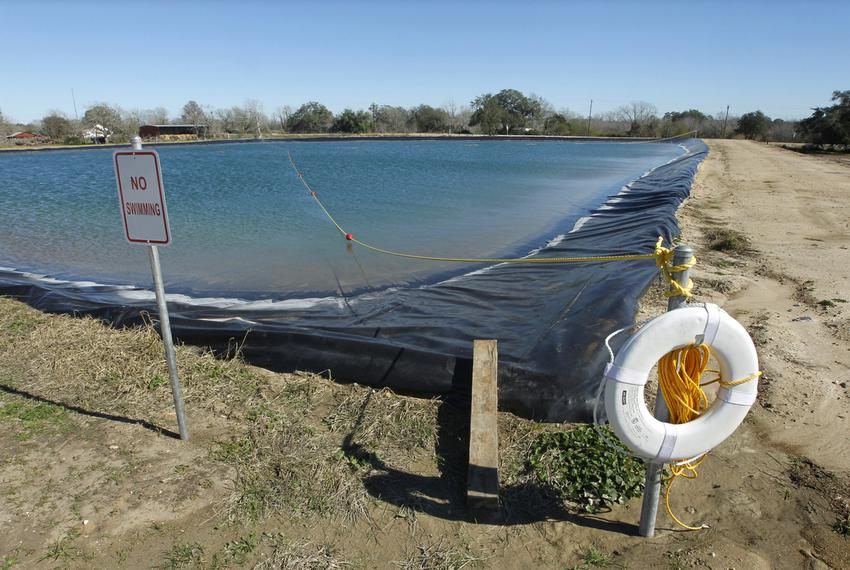 "Field distribution water tank used in the fracking process of natural gas well drilling in DeWitt County, Texas, complete with life buoy and ""No Swimming"" sign."