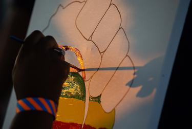 """Robyn Sims paints at her Creative Tingz shop stand during the """"I Am Juneteenth"""" festival at the Panther Island Pavilion in Fort Worth on June 19, 2021."""