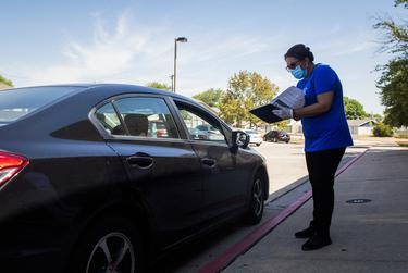 Round Rock ISD food service worker Angela Alba talks with a family during a curbside meal distribution at Bluebonnet Elementary School on Aug. 20, 2020 in Round Rock.