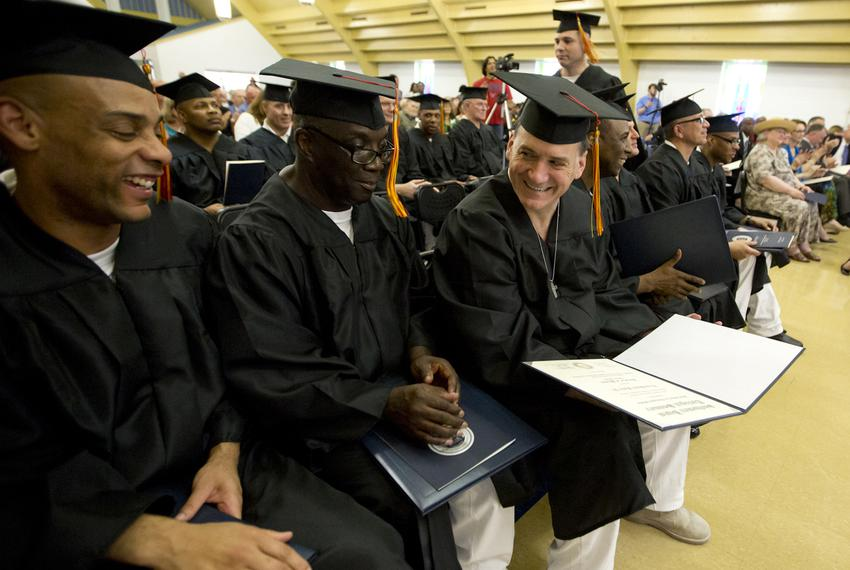 Graduates Vondre Demond Cash (from left) and Gary L. Everett smile at fellow graduate Troup Hubert Foster Jr., as he shows...