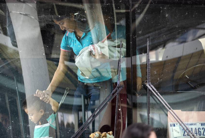 A young boy is escorted off of an immigration bus by a woman at the McAllen Central Station in downtown McAllen on June 25...