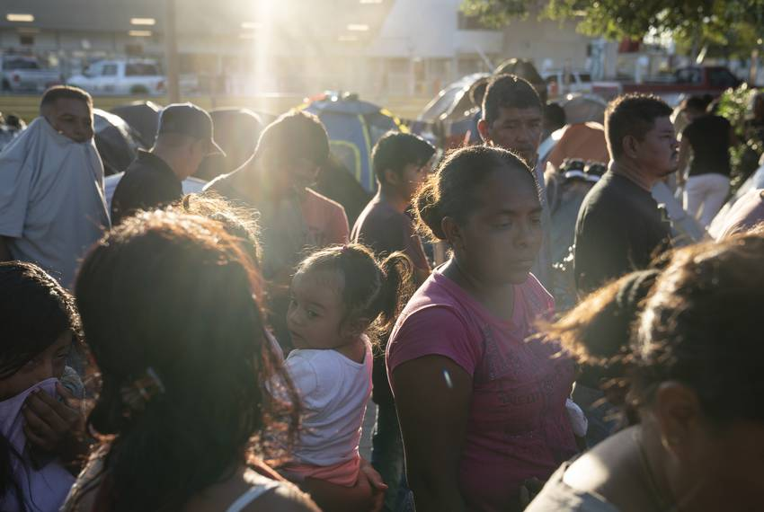 Asylum seekers wait in line to get a meal provided by Team Brownsville near the Gateway International Bridge in Matamoros,...