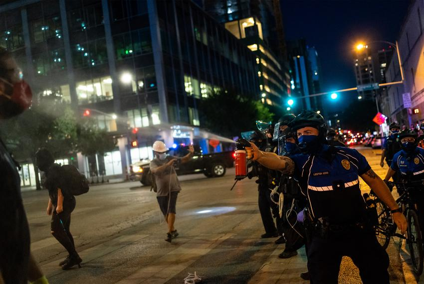 A police officer sprays a protester with pepper spray as demonstrators clash with police in riot gear in downtown Austin o...