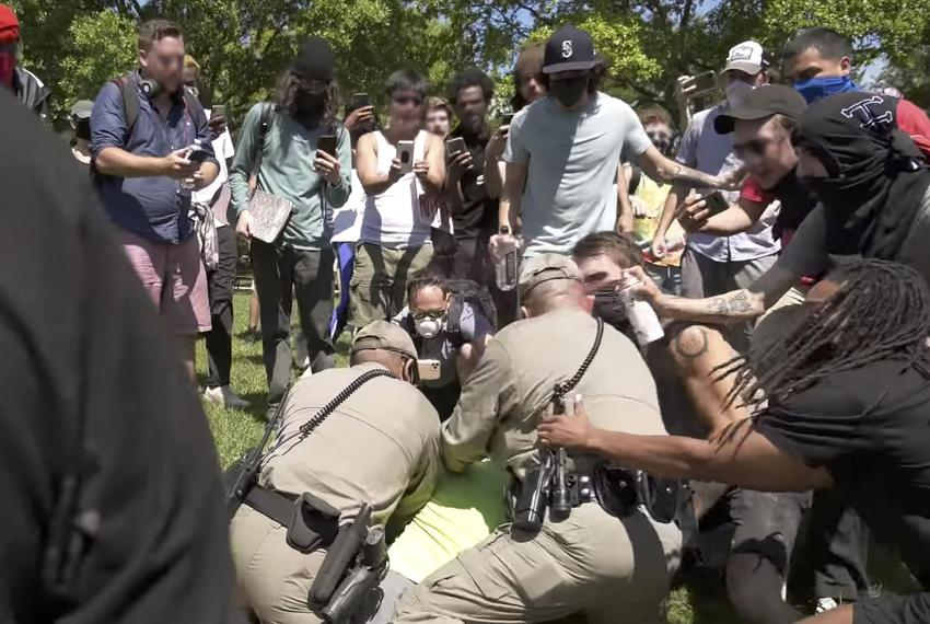 A protester sprays a DPS officer with a red liquid during the George Floyd protest at the state capitol on May 31, 2020.