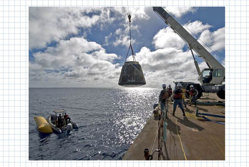A crane lifts SpaceX's Dragon spacecraft on to a barge after the vehicle twice orbited the Earth in December of 2010.