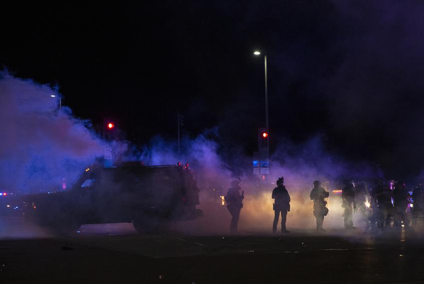 Dallas Police tactical officers stand amongst a cloud of tear gas and smoke after they fired it at protesters during a march…