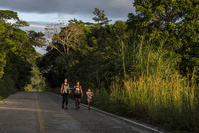 "Honduran migrants walk through highway México 307 on Oct. 21 near Palenque, Chiapas. The highway is also known by the locals as ""El gran corredor del pacífico del migrante,"" or ""The Great Pacific Corridor of the Migrant. This is a common route for Honduran migrants due to its proximity to their country."