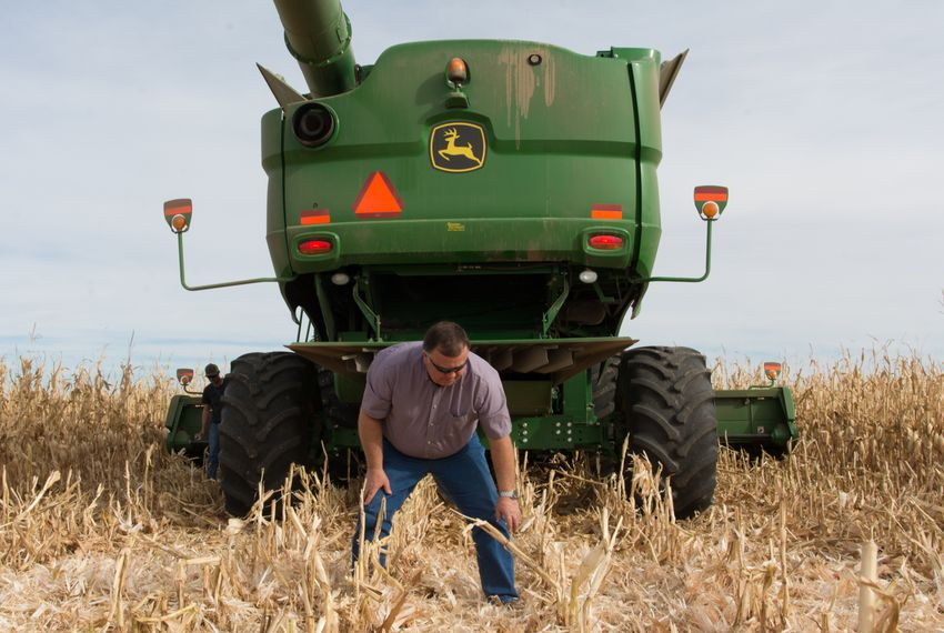 Dumas-area farmer Dee Vaughan checks the ground after a short test run in one of his combines. Vaughan has been farming since 1978 and worries increasing corporate control of agriculture may price farmers out of their jobs.