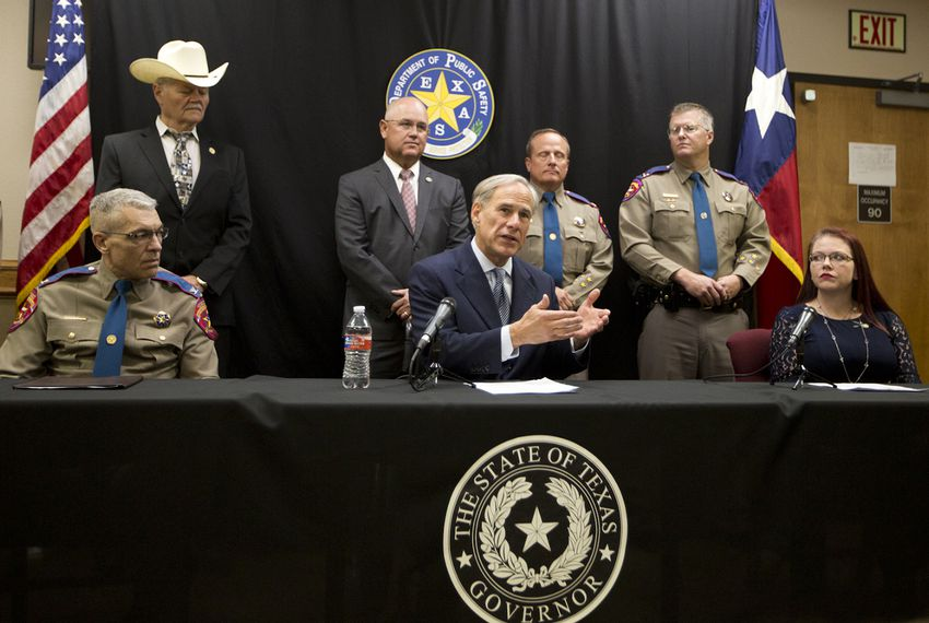 Gov. Greg Abbott. joined by DPS Director Steve McCraw (seated, left) and Kasey Allen, widow of Damon Allen, speaks at a press conference in Waco on August 7, 2018. Abbott announced a proposal to reform the bail system in Texas. The proposal is in honor of State Trooper Damon Allen, who was killed while on duty in 2017.