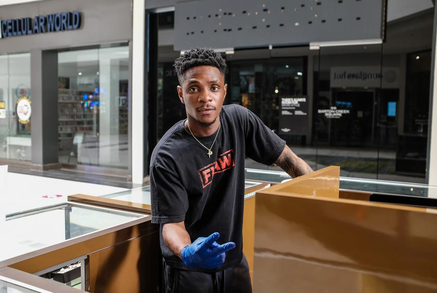 Yanick Almeida, 23, works at one of the jewelry kiosks at the Barton Creek Square Mall in Austin. The mall recently opened...