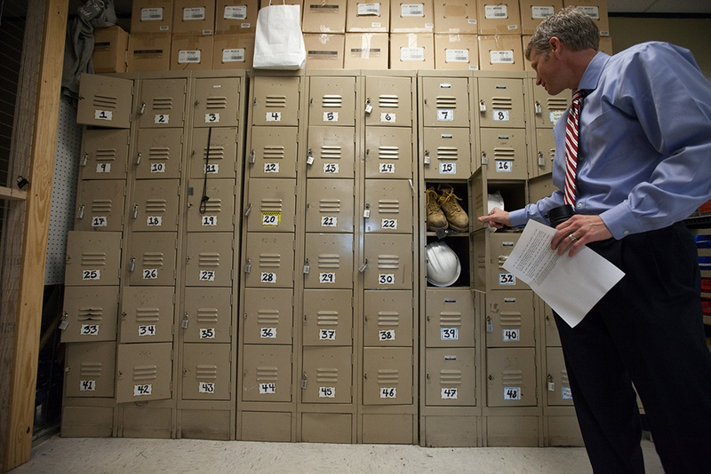 Parc Smith, CEO of American YouthWorks, a dropout recovery charter school facing closure by the state, looks in a student locker.