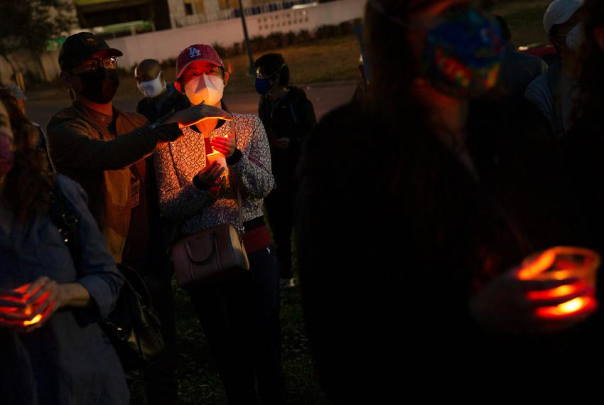 Wei Lin shields the flame of Marina Liu's candle during a rally and vigil held at the Grassy Knoll in Dallas in solidarity w…