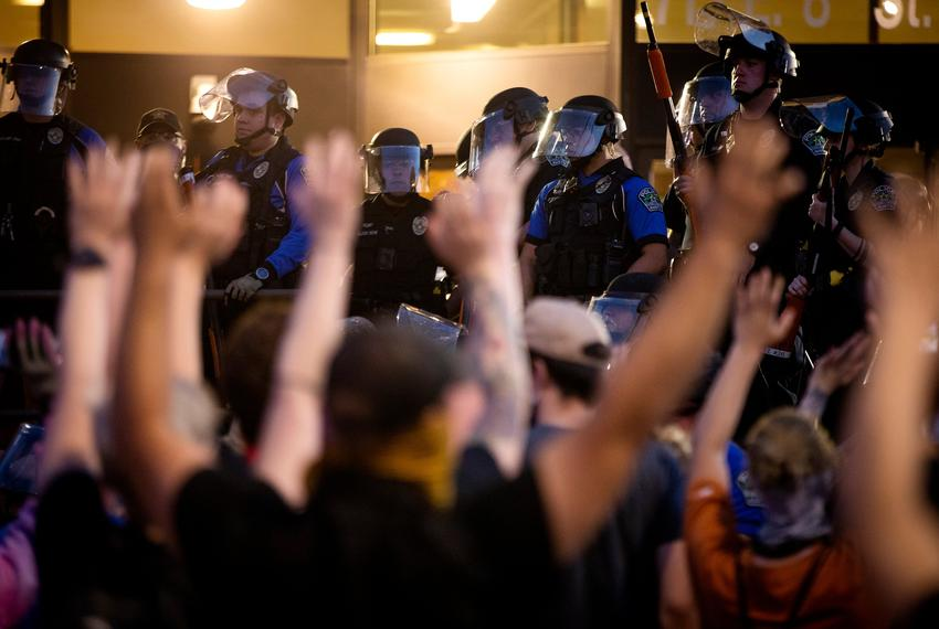"Protesters raise their arms and chant, ""Don't shoot!"" after Austin police officers fired tear gas and rubber bullets at th..."