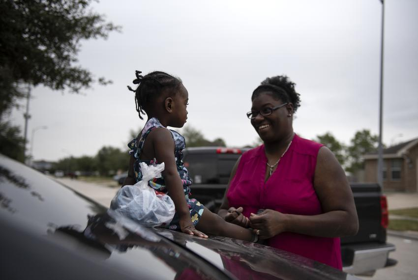 Krystol Allen ties her daughter Alexis' shoes while picking her up from daycare in Houston, Texas, Friday, Nov. 22, 2019