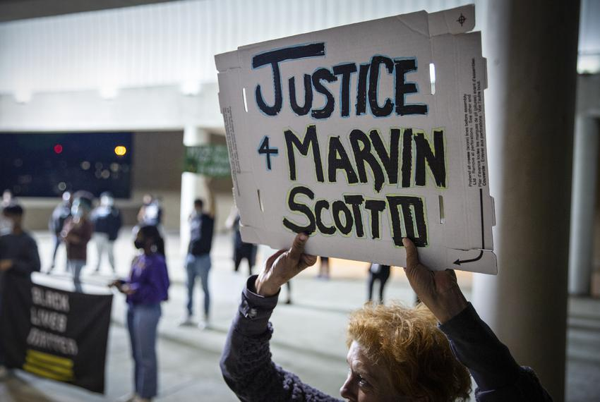 Shannon Borders holds up a sign at a demonstration outside of the Collin County Jail to demand justice for Marvin Scott III,…