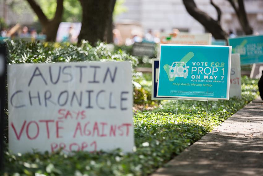 Pro and against signs of Austin's Prop 1 ride-hailing vote posted along voting centers on University of Texas at Austin's ca…