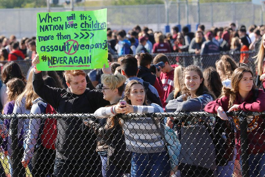 Students stand outside Marjory Stoneman Douglas High School on March 14, 2018, as part of a National School Walkout to honor the 17 students and staff members shot to death at the school in Parkland, Florida, a month before.