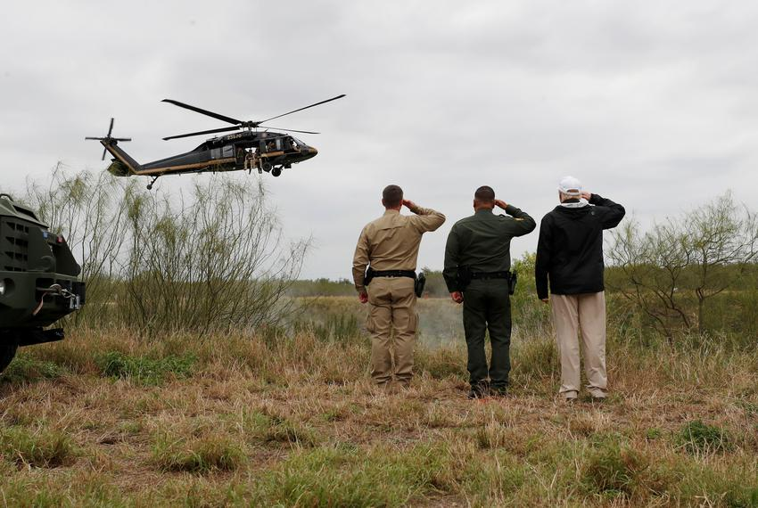 President Donald Trump and U.S. Customs and Border Protection agents salute a U.S. Border Patrol helicopter with as it flies…
