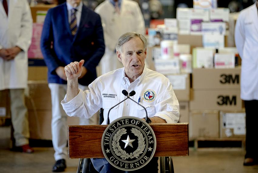 Gov. Greg Abbott gestures to boxes of personal protective equipment during a press conference about the state's response to …