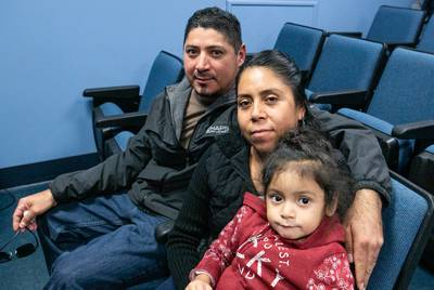 Eliecer Arce, Enedina Puente and their daughter, Melissa Arce pose for a portrait in the waiting room at Community Eye Clinic where Eliecer had a follow up appointment. They also have a child in kindergarten and one in eighth grade.