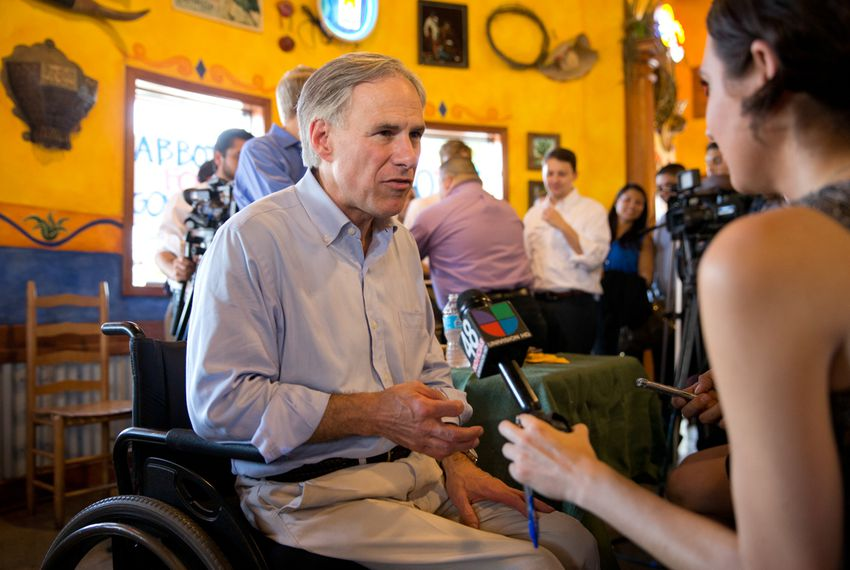 Texas Attorney General Greg Abbott speaks with a reporter for Univision on July 16, 2013, during a gubernatorial campaign event at El Pato restaurant in McAllen.