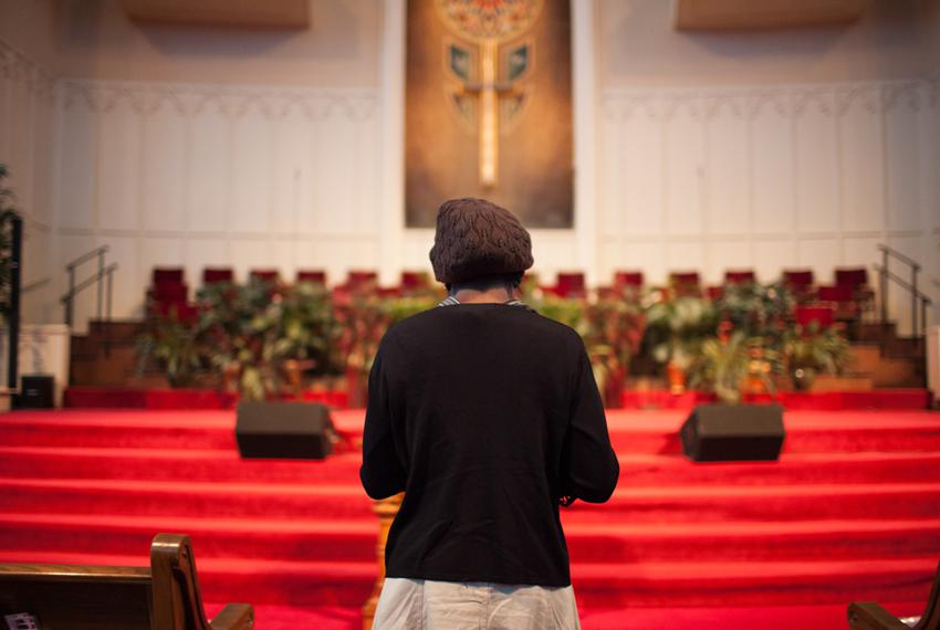 A woman, who asked not to be identified because she fears for her safety, stands near the pulpit at the end of service at Fi…