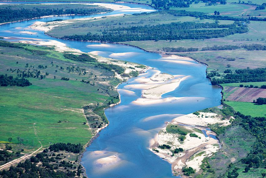 A view of the Red River looking east, north of Bonham, Texas. Texas is to the right, and Oklahoma is on the left. The border between the two states runs along the south (right) bank of the river.