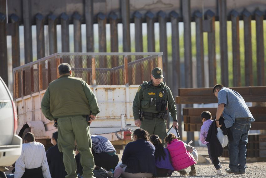 Customs and Border Protection officials detain a migrant group near the Paso del Norte International Bridge.