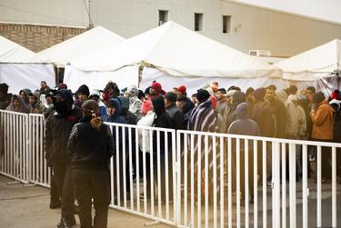 Migrants wait in line to purchase food items from a trailer located outside of the shelter where they're currently being held. According to José Luis Pliego Corona, the Secretario de Seguridad Pública of Coahuila, an estimated 1700 to 1800 migrants are currently at the shelter. Feb. 9, 2019.