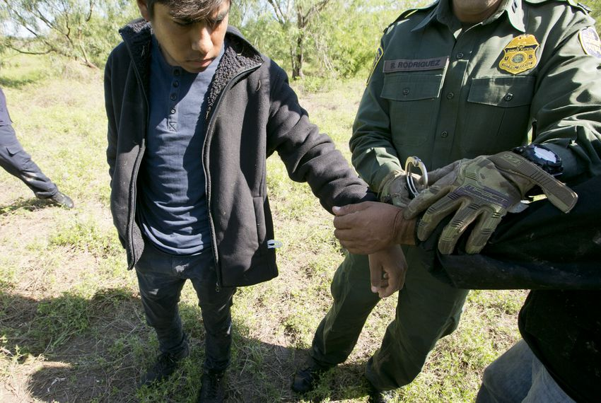 Border Patrol Agent Roberto Rodriguez handcuffs two Mexican nationals apprehended near the Texas-Mexico border on Oct. 12, 2017.