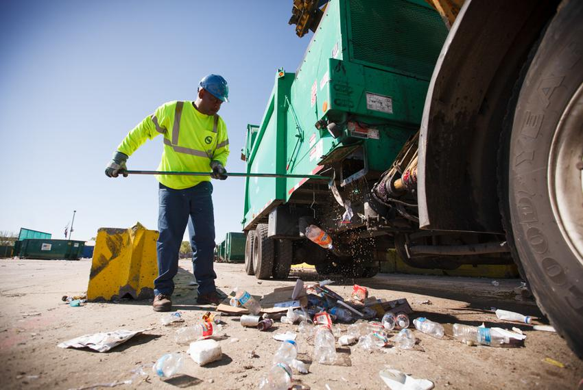 Glenn Bailey cleans out the Houston recycling truck he drives after dropping off a load at a waste management facility on Ma…