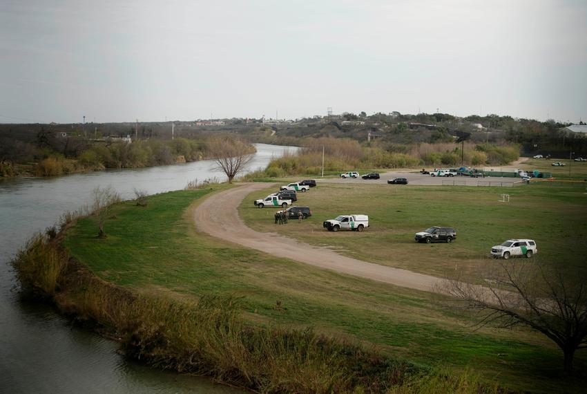 U.S. border patrol cars are seen through the fence of the bridge connecting Eagle Pass with Piedras Negras, Mexico, near the…
