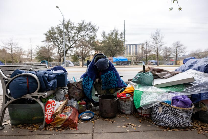 A homeless Austinite wears extra blankets to protect against the cold as an unprecedented winter storm grips much of Texas o…