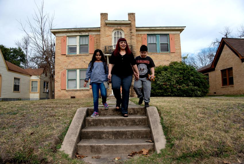 Melissa Romo and her children Mia and Zavier in front of their home on San Antonio's West Side.