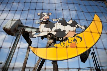 """""""Cow Jumping Over Moon,"""" a pumpjack in Luling decorated by artist George Kalesik. Luling, a tapped-out oil town once known as Texas' """"toughest,"""" has found a unique way to celebrate its heritage: decorating its aging pump jacks with a full cast of characters."""